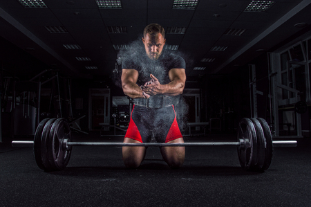 Ahlete kneels in the gym before the bar and claps his hands after which the dust from the chalk flies