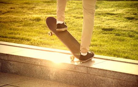 unsafe: Desperate skateboarder performs dangerous movement on the skateboard at sunset Stock Photo