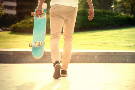 Guy with a skateboard strolls in a park under the scorching sunlight