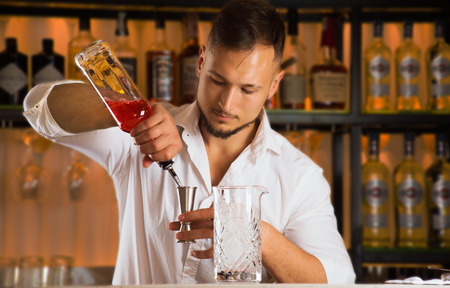 Charming barman pours alcohol from a bottle into a jigger to make a mixed drink in a mixing bowl