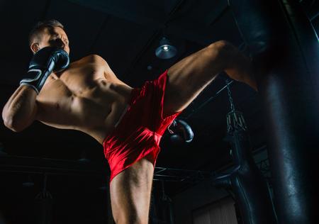 De vechter van gemengde vechtsporten slaat de zak met zijn linker voet aan de zijkant
