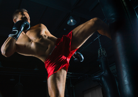 The fighter of mixed martial arts beats the bag with his left foot on the side Stock Photo