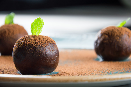 truffe blanche: Three elegant cakes in the form of balls decorated with a mint leaf