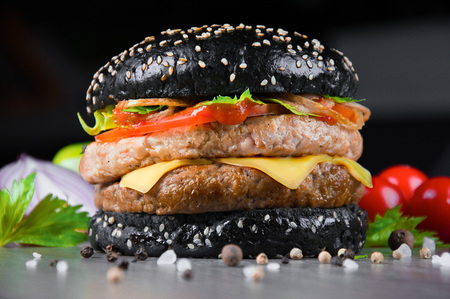 Delicious black juicy burger with fresh tomatoes, peppers and herbs. Mixed media