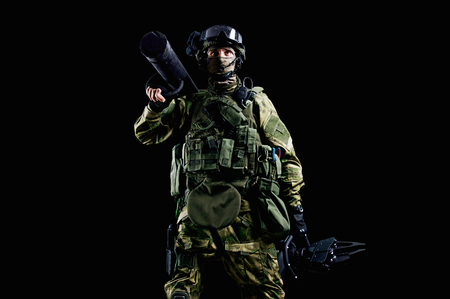 The soldier of the special unit stands in military uniform with a ram on his shoulder and a device for opening the doors. Mixed media