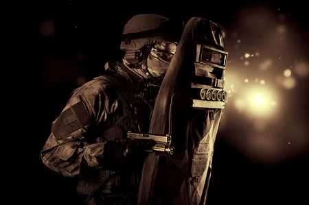 Armed with a pistol, a military man in a bulletproof vest covers himself with a shield. Mixed media Stock Photo