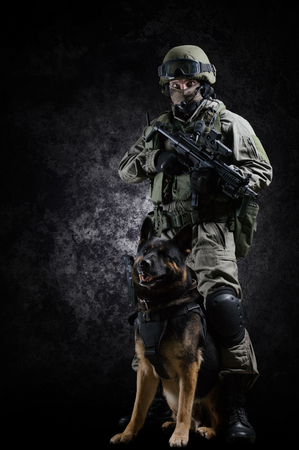 Armed soldier of a special unit with a machine gun stands with his shepherd. Mixed media Stock Photo
