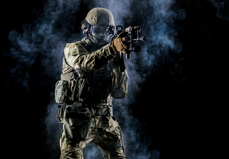 American soldier in combat ammunition with weapon in the hands of equipped laser sights is in battle order. Mixed media Stock Photo - 89045699