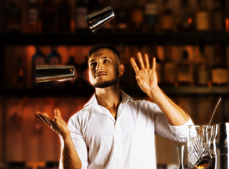 Fantastically beautiful bartender tosses two shakers into the air and arranges a real show for their guests. Mixed media