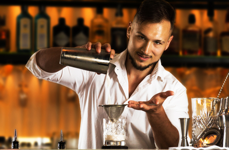 Charming bartender prepares a delicious cocktail for his guest. Mixed media