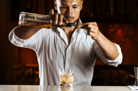 Charming barman elegantly prepares a mixed drink by pouring all the ingredients into a bar spoon. Mixed media