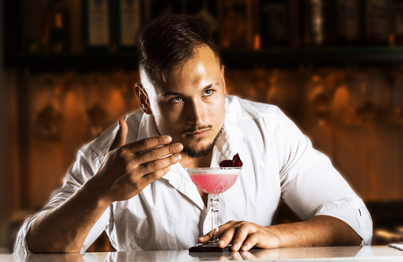 Fantastically charming bartender enjoys the aroma of a freshly prepared mixed drink. Mixed media