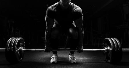 Un hombre enorme se está preparando para realizar un ejercicio llamado peso muerto. Técnica mixta Foto de archivo