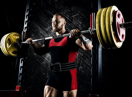 Atleta profissional se prepara para agachar com uma barra. Mídia mista