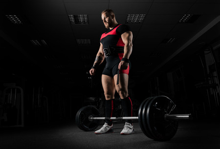 The weightlifter is preparing to perform an exercise called deadlift. He stands directly above the barbell and looks at it. Stock Photo