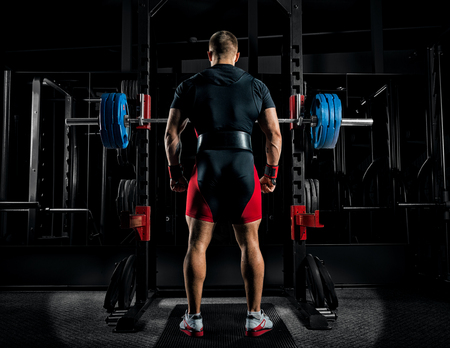 Professional athlete stands in front of the bars with a barbell and is about to crouch with her. Back view Stock Photo