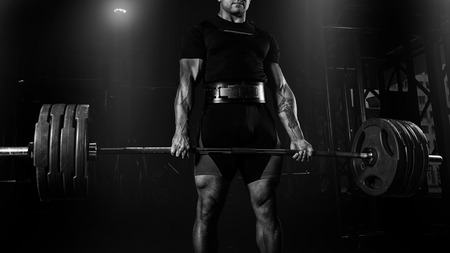 Professional athlete is standing and is holding a very heavy barbell. Front view