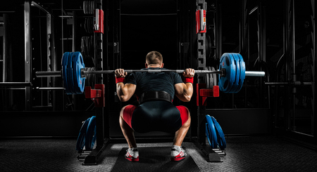 Professional athlete sits with a barbell on his shoulders and prepares to stand with her. View from the back. Stock Photo