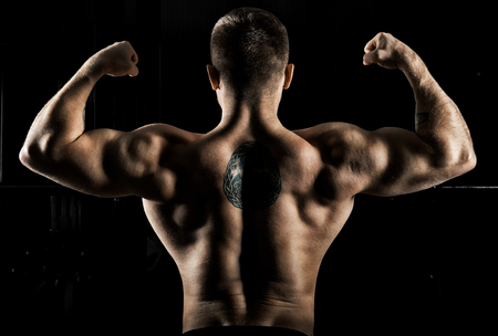 Huge weightlifter is standing with his back to the camera and straining his hands demonstrating a double bicep. Back view Stock Photo