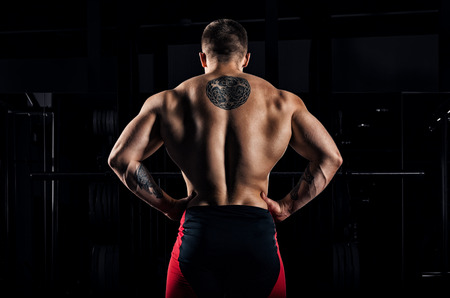 Huge weightlifter stands with his back to the camera and shows his huge back. Back view