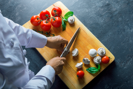 Professional chef cuts vegetables with a sharp knife from Damascus steel. Mixed media Stock Photo