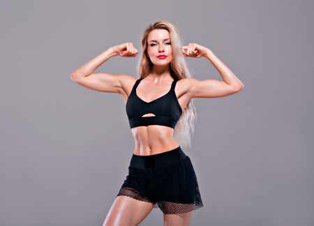 Charming sports girl posing in sports clothes and showing biceps. Mixed media Фото со стока