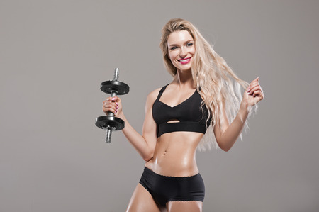 Beautiful athlete posing with a dumbbell in the studio. Mixed media