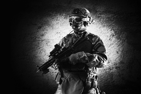 Special unit soldier stands with a gun in his hands and looks ahead. Mixed media Imagens - 115842536