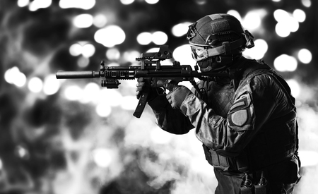 Special unit soldier stands with a gun in his hands and looks ahead. Mixed media Imagens - 115842541