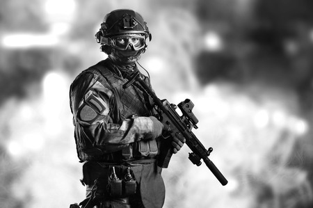 Special unit soldier stands with a gun in his hands and looks ahead.