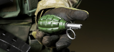 The soldier in full combat ammunition holds a grenade in his hand.