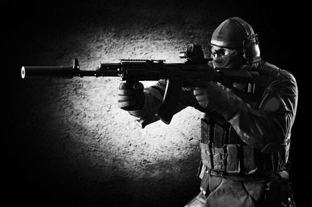 Special unit soldier stands with a gun in his hands and aims at the target. Imagens