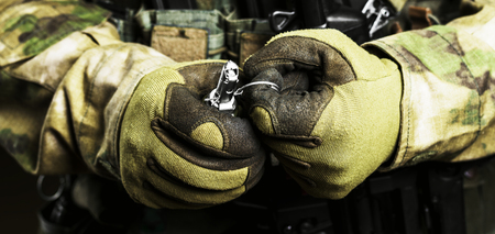 Soldier in full combat ammunition pulls a check from a grenade. Imagens