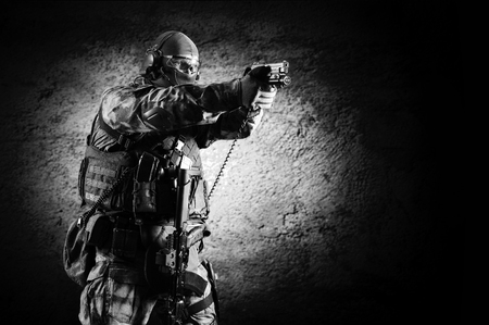 Special unit soldier stands with a pistol in his hands and aims at the target. Imagens