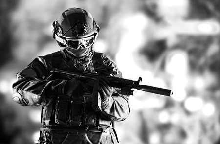 Special unit soldier stands with a gun in his hands and looks ahead. Imagens - 115842806