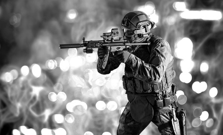 Special unit soldier stands with a gun in his hands and looks ahead. Mixed media Imagens - 115843030
