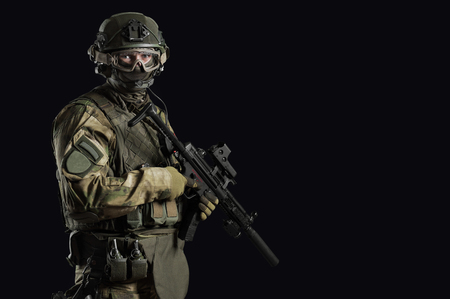 Special unit soldier stands with a gun in his hands and looks ahead. Mixed media Imagens - 115859398