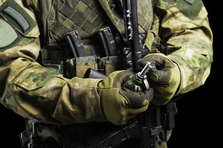 Soldier in full combat ammunition pulls a check from a grenade. Mixed media Imagens - 115859593