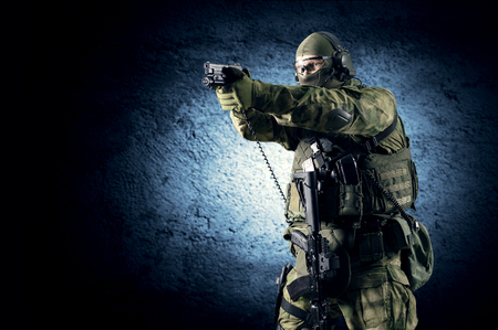 Special unit soldier stands with a pistol in his hands and aims at the target. Mixed media Imagens - 115859612