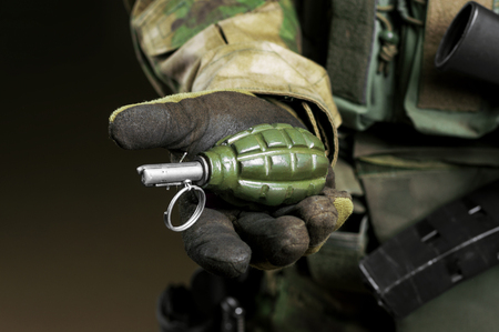 The soldier in full combat ammunition holds a grenade in his hand. Imagens - 115859660