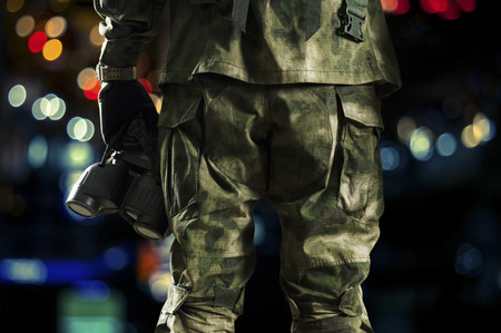 Special unit soldier holds a night vision device in his hand.