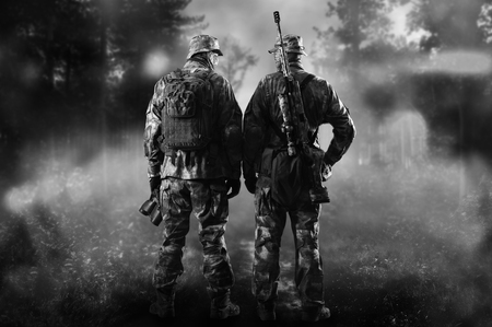 Two soldiers of a special unit are standing in a smoky forest.