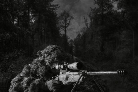 The sniper in disguise lies with a sniper rifle and aims at the telescopic sight. Imagens - 115911686