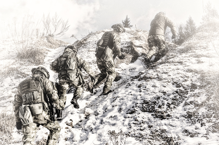 Group of special forces climbs into the mountains in order to take a favorable position to protect the target. Mixed media Imagens