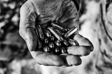 The fighter holds a handful of bullets in his palm for weapons. Mixed media Imagens