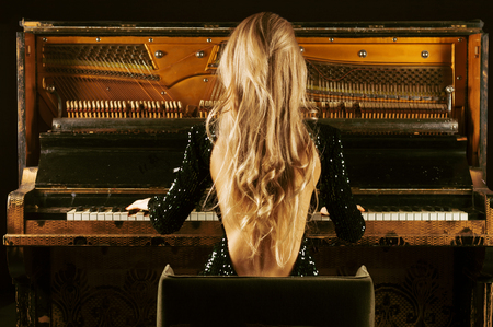 The charming girl in an evening dress plays the old German piano. Back view. Conceptual media