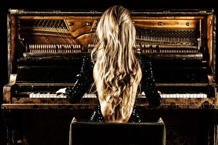 Delightful girl with luxurious long hair plays a retro piano. Back view. Mixed media