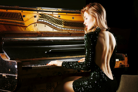 Charming girl in evening dress posing near the old German piano. Back view. Mixed media Stockfoto