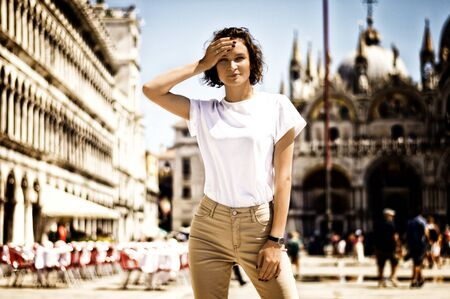 Professional model stands in St. Marks Square and poses in front of the camera. Italy travel concept. Mixed media