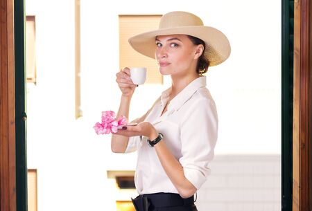 Charming woman in a stylish suit and elegant hat stands in a hotel room and drinks Italian aromatic coffee. Tourism and leisure concept. Mixed media